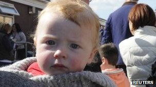 11 month old baby boy held in his father's arms as they queue outside Morriston Hospital in Swansea