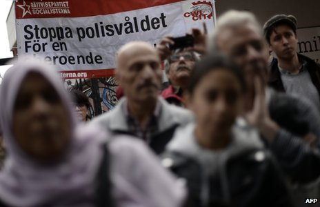 People stand in front of a banner reading 'Stop police violence for an independent investigation' during a demonstration against police violence in the Stockholm suburb of Husby (22 May 2013)