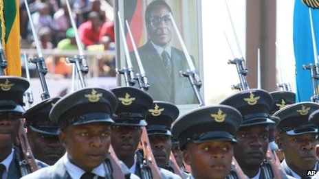 "Soldiers march with a photo of Zimbabwean President elect, Robert Mugabe, in the background, during the country""s commemoration of Defence Forces Day,"