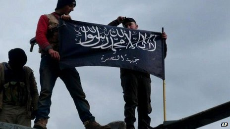 Members of the al-Nusra Front raise its banner above a military base in Idlib province (11 January 2013)