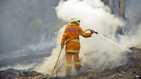 A New South Wales Rural Fire Service volunteer puts out a spot fire in Bell on 20 October 2013