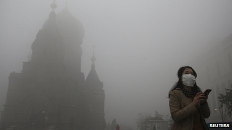A woman wearing a mask checks her mobile phone during a smoggy day on the square in front of Harbin's landmark San Sophia church, in Heilongjiang province