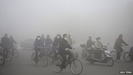 People ride along a street on a smoggy day in Daqing, Heilongjiang province, 21 October 2013