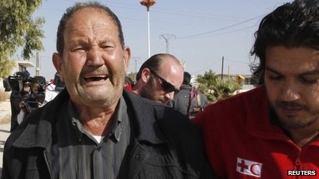 A volunteer from the Syrian Arab Red Crescent helps a weeping man