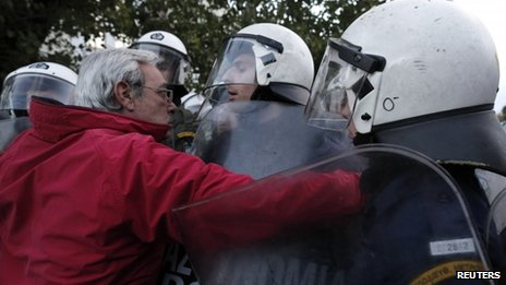 A protester remonstrates with policemen as he tries to approach the headquarters of former state broadcaster ERT
