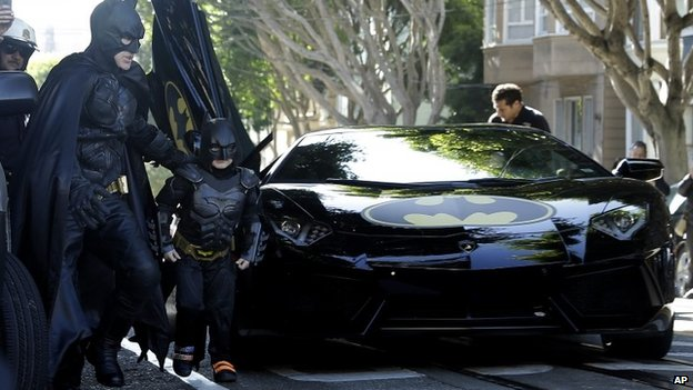 Miles Scott, dressed as Batkid, exits the Batmobile with Batman to save a damsel in distress in San Francisco, on 15 November 2013