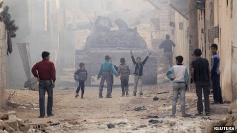 Children run after a tank driven by fighters from the Tawhid Brigade, in Aleppo, November 11, 2013