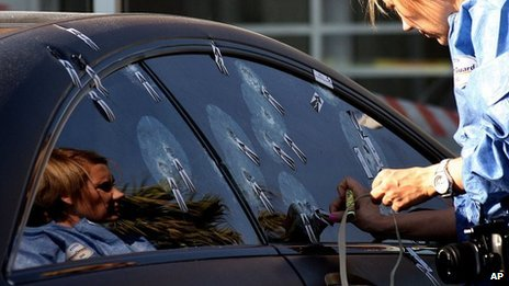 "Unidentified ballistics investigator comb the scene of Radovan Krejcir""s bullet-proof car after he escaped an attempt to kill him in Johannesburg, South Africa, Wednesday July 24, 2013."