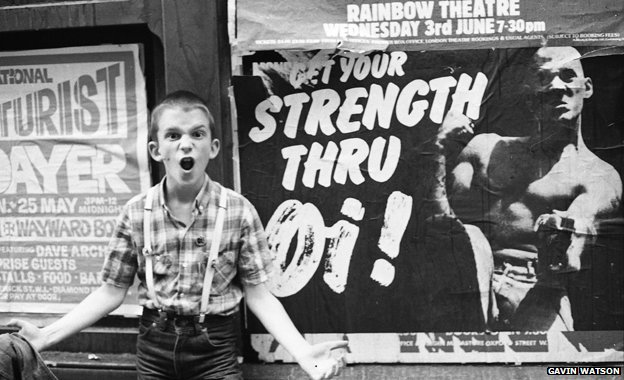 "Photographer Gavin Watson's brother stands in front of a ""Strength thru Oi!"" poster featuring Nicky Crane"