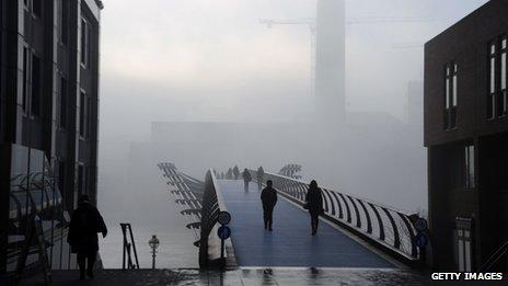 La gente que camina a través de una espesa niebla en el Puente del Milenio sobre el río Támesis