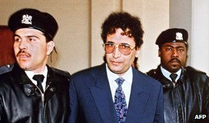 Convicted Lockerbie bomber Abdelbaset Ali Mohmet al-Megrahi (C) is escorted by security officers in Tripoli, February 1992