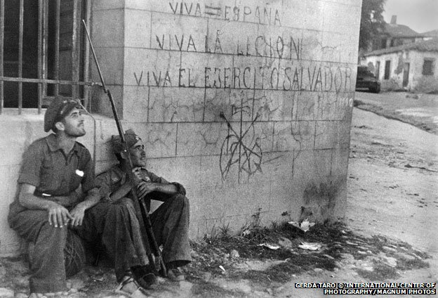 Two soldiers sitting by a wall