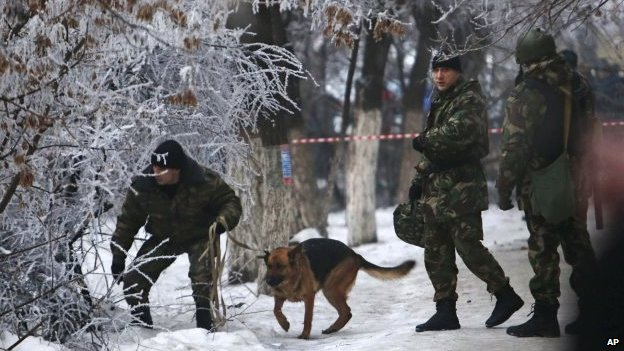 Police officers with a sniffer dog examine territory around the site of a trolleybus explosion in Volgograd, Russia, Monday, Dec 30, 2013.