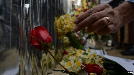 Afghan activists place flowers as they pay tribute to the victims of an attack two days ago, in front of the restaurant on 19 January