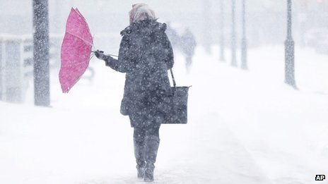 A pedestrian's umbrellas is upset during a winter snowstorm in Philadelphia 21 January 2014