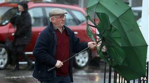 A man struggling to hold an umbrella in Ballymena