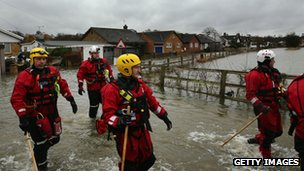 A river level assessment team make their way towards flooded houses next to the Thames River