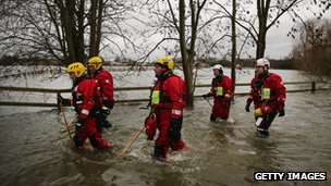 A river level assessment team make their way towards flooded houses in Shepperton in Spelthorne, Surrey