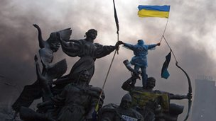 Protesters scale a statue in Independence Square