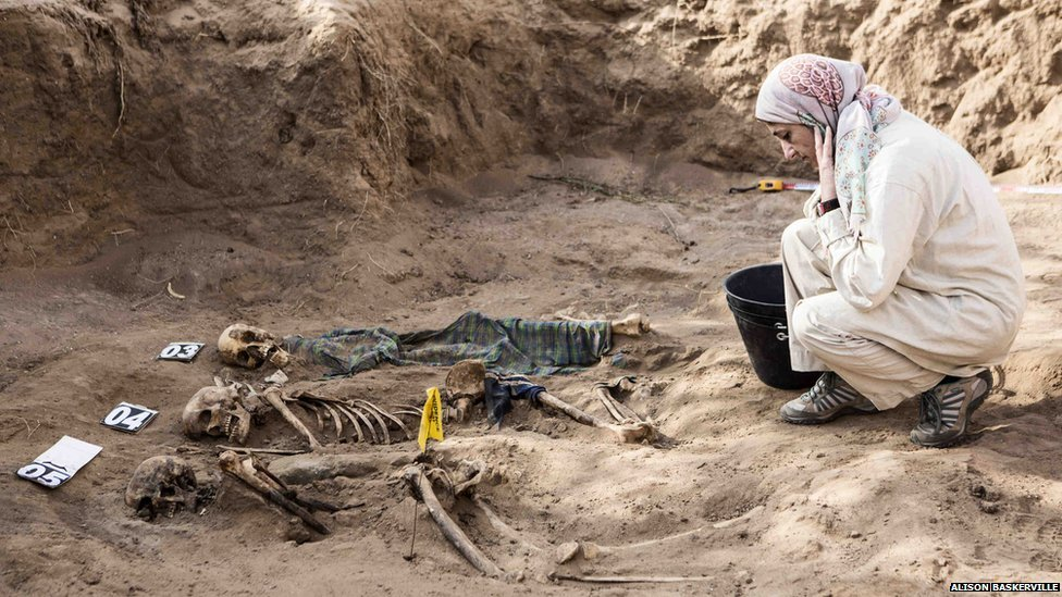 A student studies the human remains in the grave