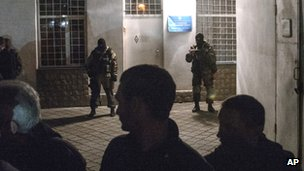 Pro-Russian activists form a human chain outside an entrance to the General Staff Headquarters of Ukrainian Navy in Sevastopol, while unidentified gunmen stand in the background