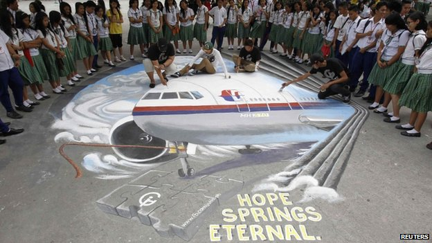 A group of artists put the finishing touches to a three dimensional artwork, based on the missing Malaysia Airlines flight MH370, that was painted on a school ground in Makati city, metro Manila on 17 March 2014