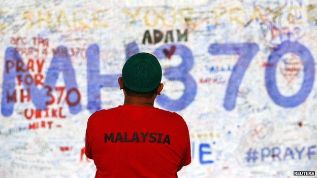 A man stands in front of a board with messages of hope and support for the passengers of the missing Malaysia Airlines MH370 at the departure hall of the Kuala Lumpur International Airport, 17 March 2014