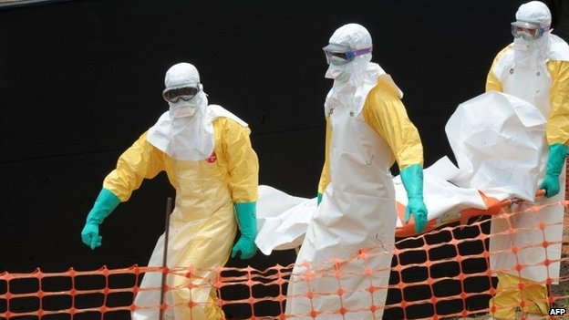 """Staff of the """"Doctors without Borders"""" (""""Medecins Sans Frontieres"""") medical aid organisation carry the body of a person killed by viral haemorrhagic fever, at a centre for victims of the Ebola virus in Guekedou, on 1 April 2014"""