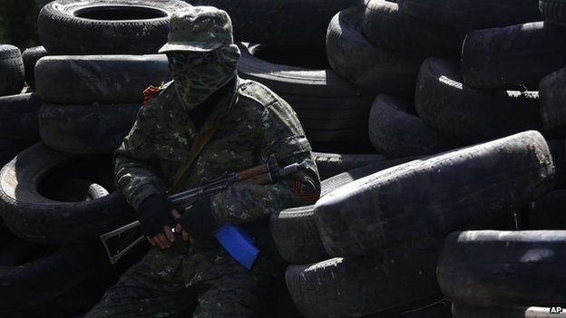 A pro-Russian armed man sits in front of the city hall in Kostyantynivka