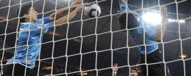 Luis Suarez (left) handles the ball against Ghana