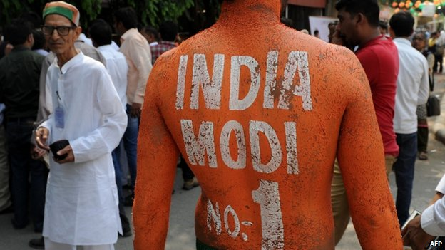 Supporter painted with a slogan supporting Modi celebrates inside BJP headquarters in Delhi 17/05/2014