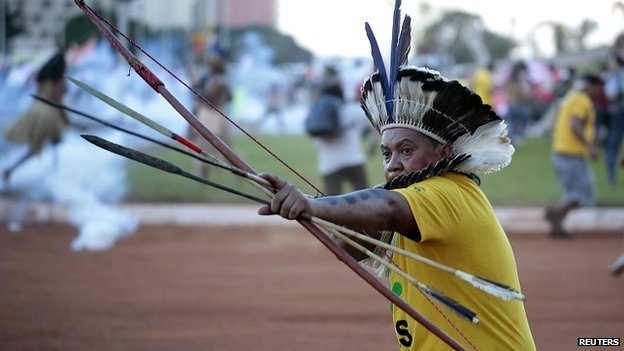 An indigenous Brazilian protesters aims an arrow at riot police who fired tear gas at demonstrators in Brasilia - 27 May 2014