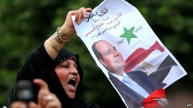 Woman holds up a poster of Abdul Fattah al-Sisi in Cairo (27 May 2014)