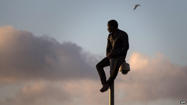 A  sub-Saharan migrant sits on top of a pole set in a metallic fence that divides Morocco and the Spanish enclave of Melilla