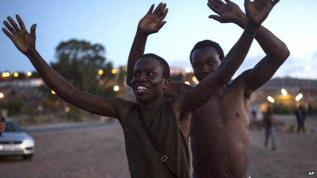 Sub-Saharan migrants react after scaling a metallic fence that divides Morocco and the Spanish enclave of Melilla