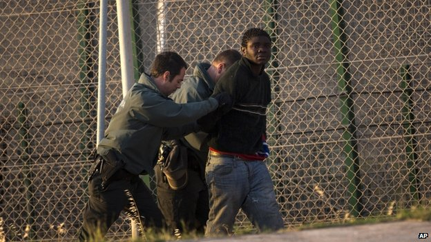 A sub-Saharan migrant is detained and sent back to the Moroccan side by Spanish Guardia Civil officers after scaling a metallic fence that divides Morocco and the Spanish enclave of Melilla