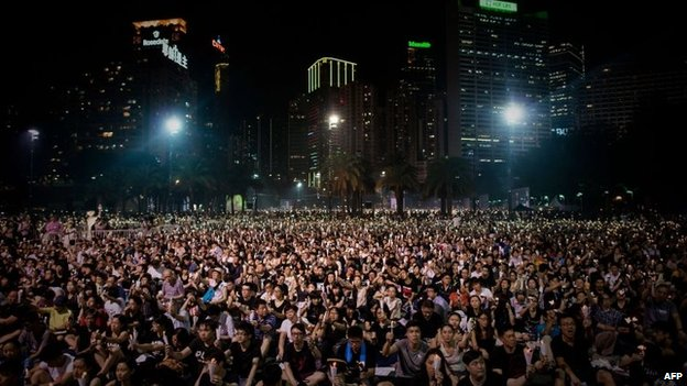 People sit together as they commemorate China's 1989 Tiananmen Square events during a candlelight vigil in Hong Kong on June 4