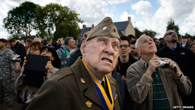 Veteran Raymond W. Sylvester, 95, watches as paratroop veterans drop into Picauville
