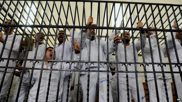 Mohammed Morsi's supporters charged with violence chant slogans against the Egyptian military during a trial. Photo: March 2014
