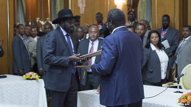 Salva Kiir (L), President of South Sudan, and Riek Machar (R), SPLM Opposition leader, hand over the Cessation of Hostilities treaty over the war in South Sudan on 9 May 2014 in Addis Ababa.
