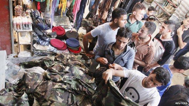 Iraqi men buy military uniforms at a shop in Basra, southeast of Baghdad, June 16