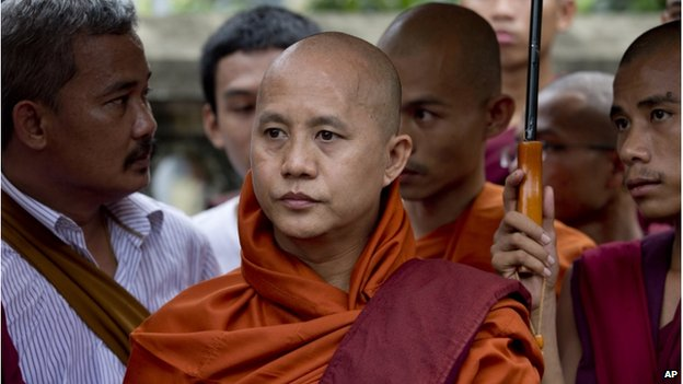 Controversial Buddhist monk Wirathu (centre) who is accused of instigating sectarian violence between Buddhists and Muslims through his sermons, stands with other monks in support of five Buddhist monks who were forced to give up their robes outside a courthouse in Yangon, Myanmar, on 20 June 2014.