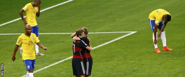Thomas Muller (left) hugs Toni Kroos with Brazil's players around them