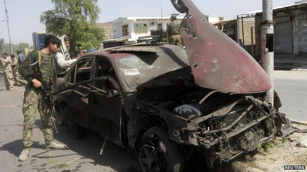 Soldier inspects blown-up car in Jalalabad (12 July 2014)