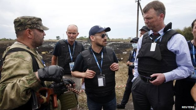 Organization for Security and Co-operation in Europe (OSCE) monitors speak with a pro-Russian separatist (left) at the crash site of Malaysia Airlines Flight MH17, near the settlement of Grabove in the Donetsk region, Ukraine, 19 July 2014