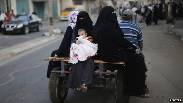 Palestinians ride in a donkey cart as they flee their houses following heavy Israeli shelling during an Israeli ground offensive east of Khan Younis in the southern Gaza Strip, 23 July 2014