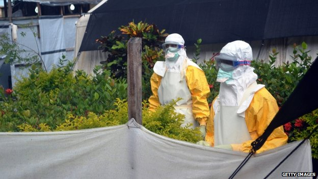 Members of Doctors Without Borders (MSF) wearing protective gear walk outside the isolation ward of the Donka Hospital, on 23 July 2014 in Conakry.