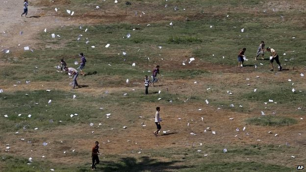 Palestinians gather leaflets dropped by an Israeli plane warning residents of Gaza City, 30 July