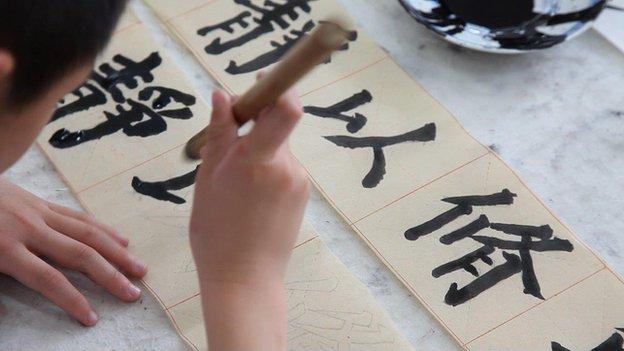 TV still of Beijing children practising Chinese calligraphy