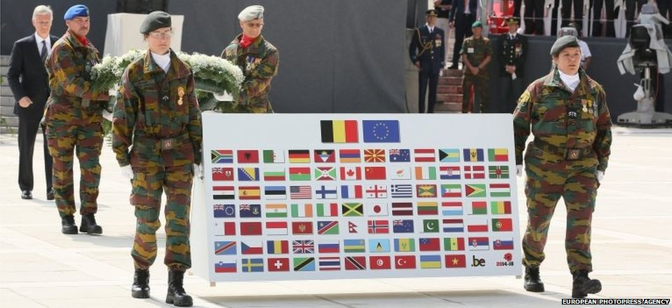 King Philippe of Belgium (far left) lays a wreath